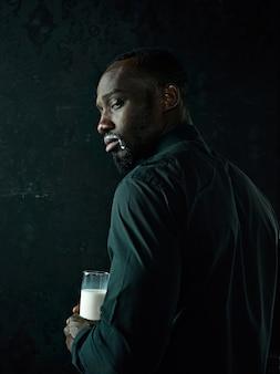 Élégant jeune homme noir africain avec une tasse blanche de café posant sur fond sombre de studio.