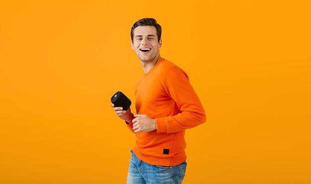 Élégant jeune homme souriant en pull orange tenant haut-parleur sans fil heureux d'écouter de la musique s'amuser sur orange