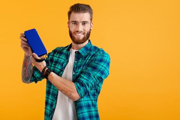 Élégant jeune homme souriant tenant haut-parleur sans fil, écouter de la musique sur orange