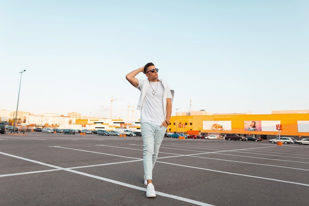 Élégant jeune homme urbain à lunettes de soleil dans des vêtements d'été à la mode en baskets à la mode en cuir blanc bénéficie d'une promenade autour de la ville. mec à la mode avec une coiffure élégante dans un parking extérieur.