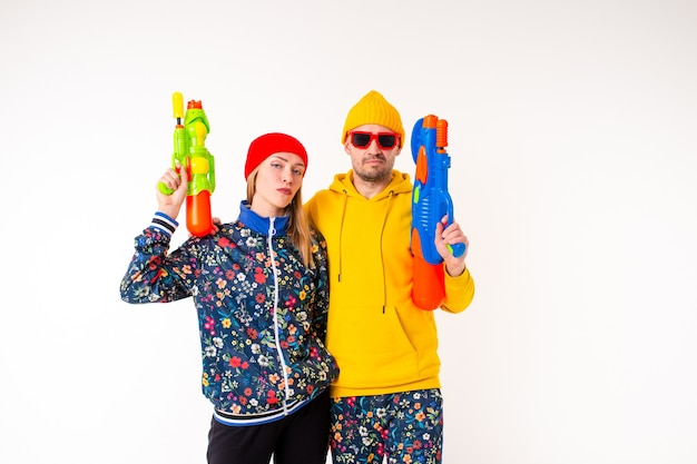 Élégant joli couple d'homme et femme dans des vêtements colorés posant avec des pistolets jouets sur un mur blanc