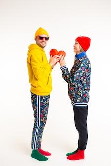Élégant joli couple d'homme et femme dans des vêtements colorés tenant coeur sur mur blanc