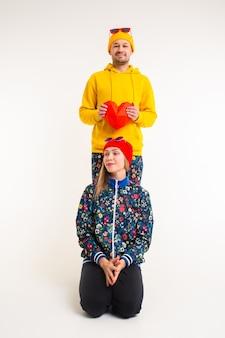 Élégant joli couple d'homme et femme dans des vêtements colorés tenant coeur