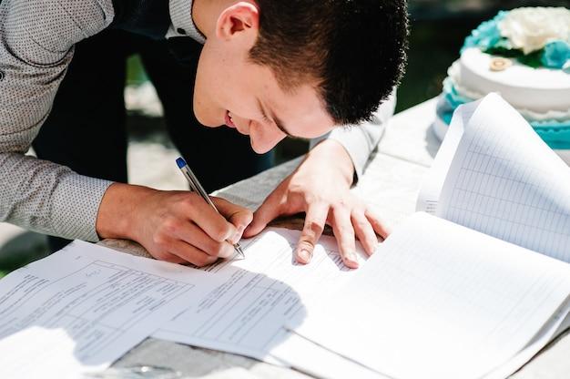 Élégant marié heureux tient un stylo dans sa main et écrit oui dans le magazine des mariages