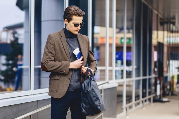 Élégant mec attrayant en veste avec passeport et billets