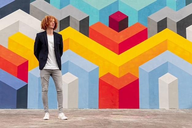 Élégant mec millénaire en tenue à la mode debout près d'un mur coloré