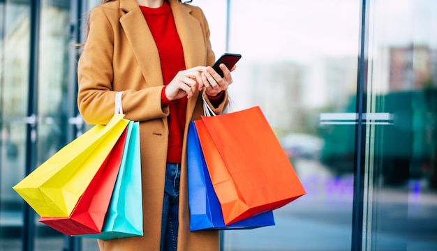 Élégant moderne belle jeune femme avec un téléphone intelligent et des sacs à provisions pendant qu'elle marche en plein air après le centre commercial