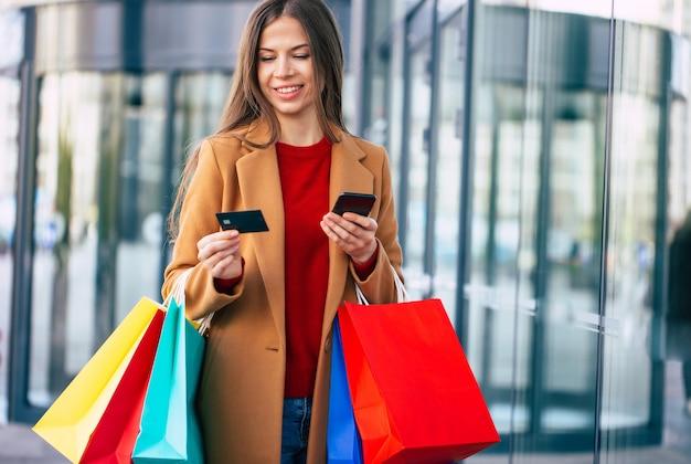 Élégant et moderne belle jeune femme avec l'utilisation d'un téléphone intelligent pour les services bancaires en ligne et les sacs à provisions pendant qu'elle marche en plein air après le centre commercial