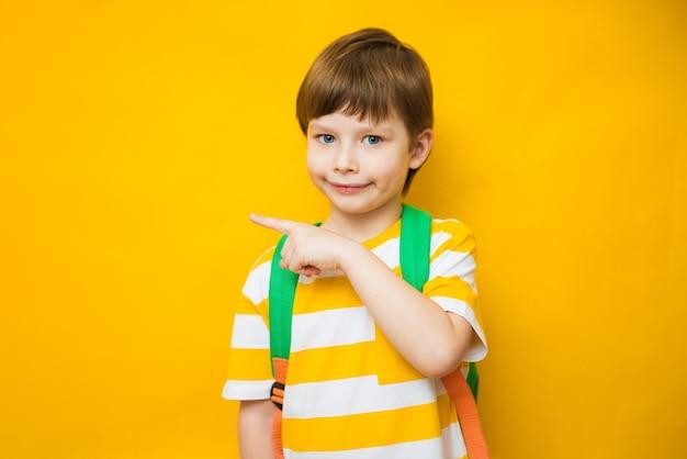 Élégant petit écolier avec doigt pointé sur fond jaune