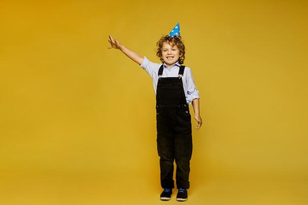 Élégant petit garçon aux cheveux roux en salopette et bonnet d'anniversaire posant sur le fond jaune, isolé. mode enfantine