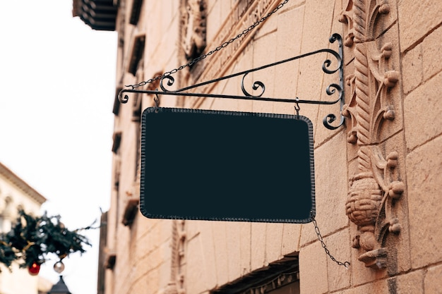 Élégant signe vierge rectangulaire dans un cadre en fer forgé est suspendu au mur de pierre d'un bâtiment ancien