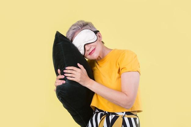 Élégante belle femme âgée avec un oreiller dans les mains sur un fond jaune