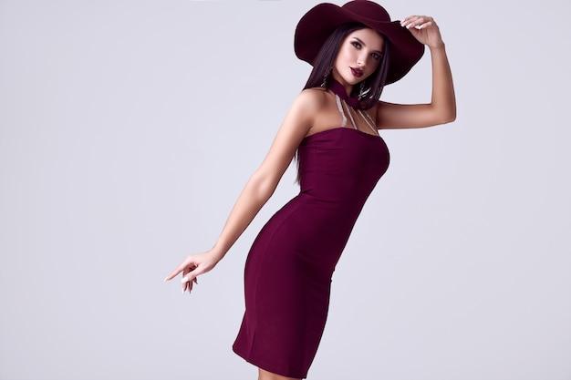 Élégante belle femme brune dans une robe colorée et large chapeau