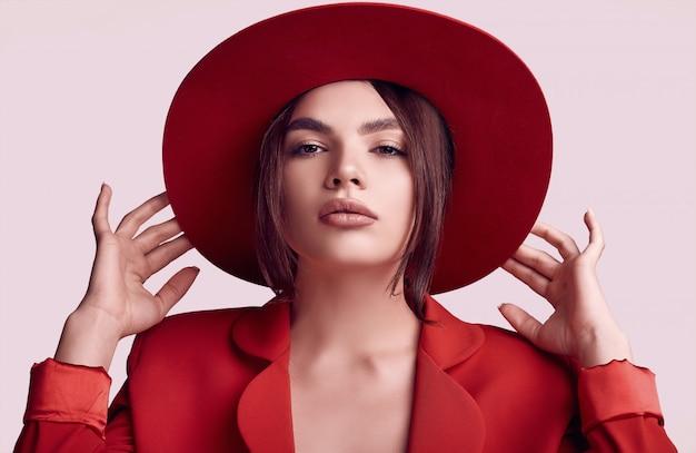 Élégante belle femme dans un costume à la mode rouge et large chapeau