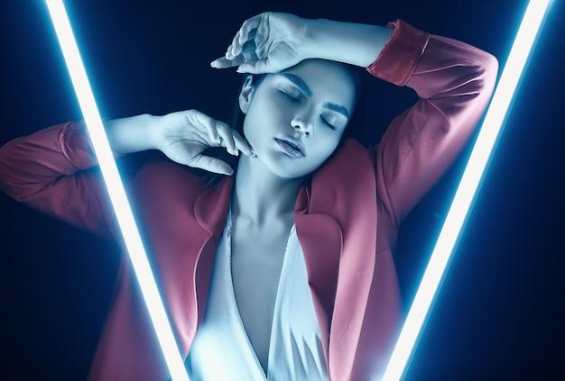 Élégante belle femme dans un costume à la mode rouge posant avec des néons