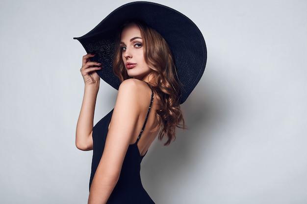 Élégante belle femme dans une robe noire et un chapeau