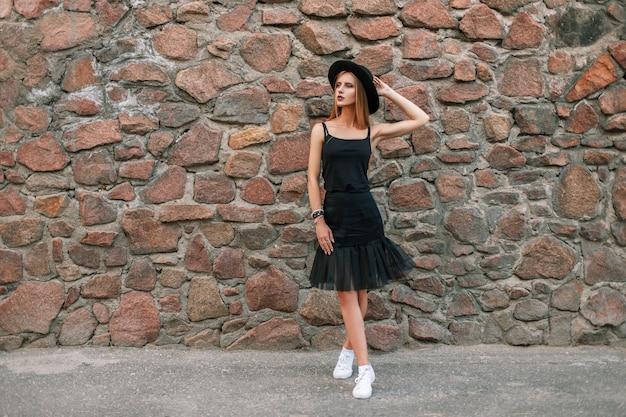 Élégante belle femme dans des vêtements noirs à la mode avec un chapeau près d'un mur de pierre