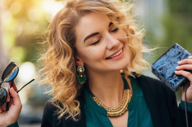 Élégante belle femme en jeans et veste marchant dans la rue avec petit sac à main, style élégant, tendances de la mode printanière