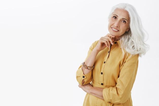 Élégante belle femme senior aux cheveux gris souriant heureux