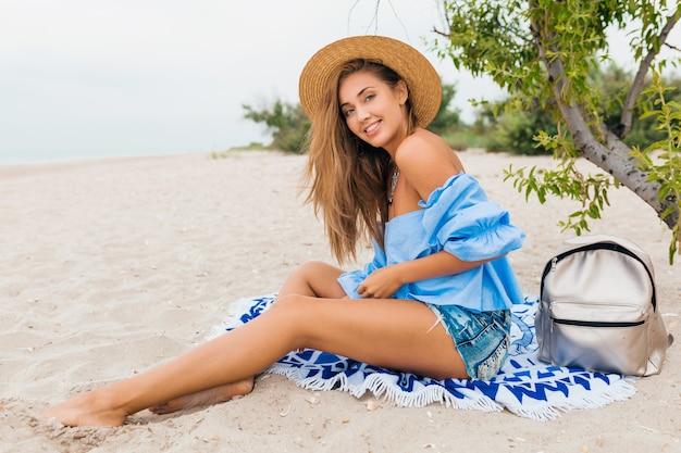 Élégante belle femme souriante assise sur le sable avec des jambes maigres en vacances d'été sur la plage tropicale portant un chapeau de paille, sac à dos argenté