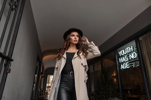 Élégante belle fille glamour aux cheveux bruns bouclés dans des vêtements de mode avec un manteau gris et un chapeau marche dans la rue