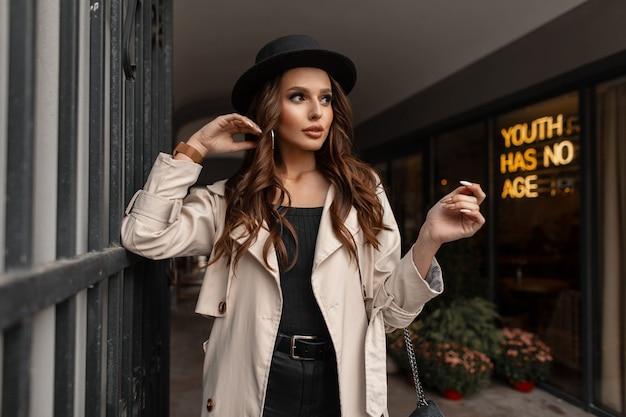 Élégante belle jeune femme aux cheveux bruns bouclés dans un chapeau à la mode avec un élégant manteau beige se promène dans la rue près d'un café. style et beauté d'automne féminins élégants