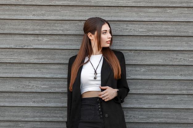 Élégante belle jeune femme dans un manteau noir fashion debout près d'un mur en bois dans la rue