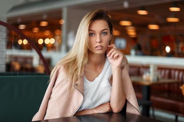 Élégante belle jeune femme dans une veste de mode rose assis à l'intérieur