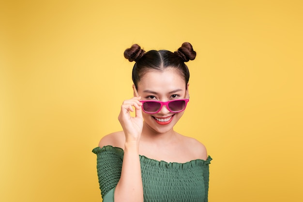 Élégante belle jeune femme à lunettes de soleil sur fond jaune.
