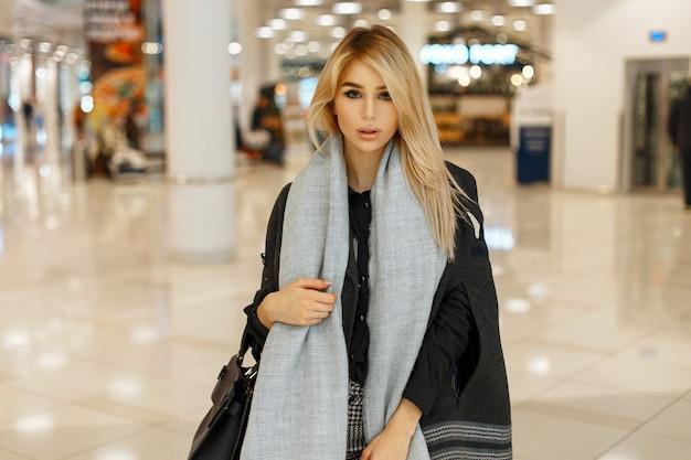 Élégante belle jeune femme en manteau automne tendance avec foulard shopping