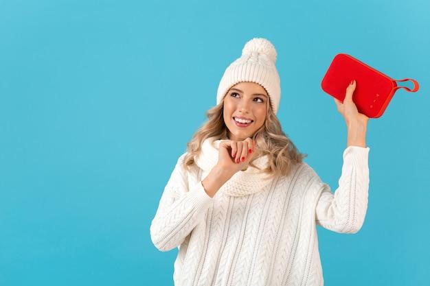 Élégante blonde souriante belle jeune femme tenant haut-parleur sans fil écouter de la musique danse heureuse portant chandail blanc et bonnet tricoté style hiver posant isolé sur mur bleu