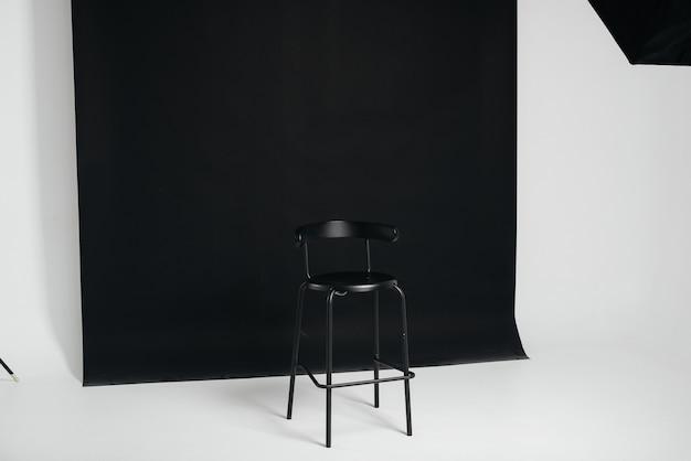 Une élégante chaise noire se dresse sur un fond noir dans la salle du studio. le concept d'un poste vacant ou d'un entretien. cinéma, chaise de réalisateur.