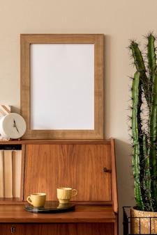 Élégante composition rétro de l'espace de travail avec armoire en bois vintage, tasse de café, pot design avec cactus, cadre photo vierge et accessoires personnels élégants