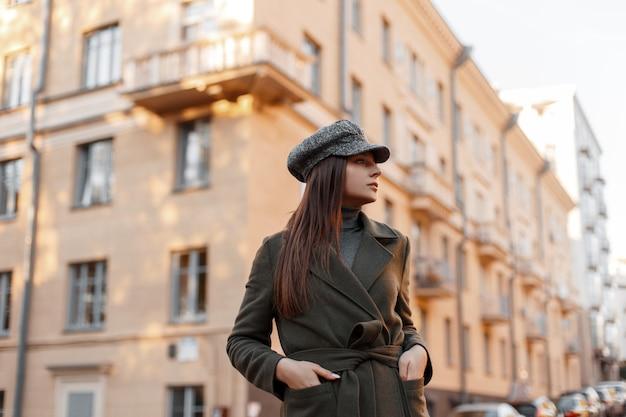 Élégante élégante belle jeune fille dans un chapeau vintage et manteau de mode marchant dans une rue européenne près du bâtiment