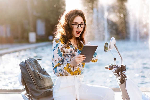 Élégante étudiante avec sac à dos en cuir et porte-cartes lisant quelque chose avec un visage surpris