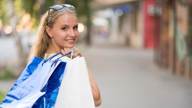 Élégante femme adulte portant des sacs à provisions