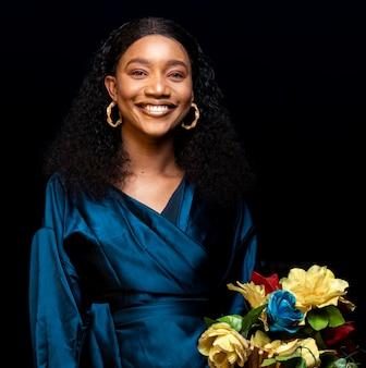 Élégante femme africaine dans des vêtements élégants tenant un bouquet de fleurs