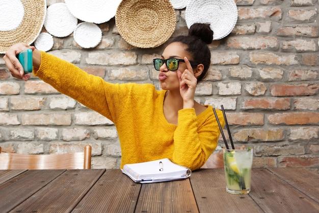 Élégante femme africaine prenant selfie au café