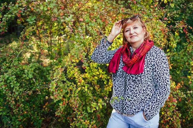 Élégante femme d'âge moyen posant dans la forêt d'automne portant des vêtements et des accessoires d'automne