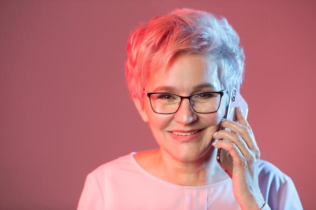 Élégante femme âgée dans des verres avec un téléphone