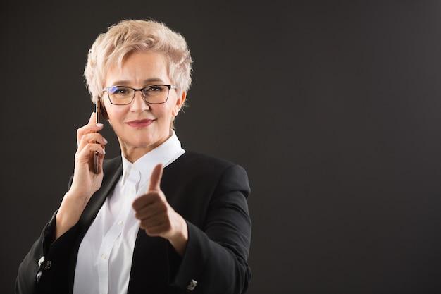 Élégante femme âgée à lunettes et dans une veste noire appelle au téléphone avec un geste de la main