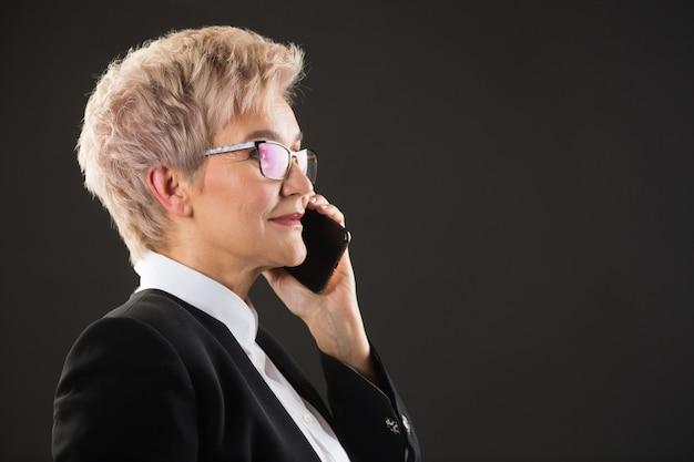 Élégante femme âgée à lunettes et dans une veste noire appelle par téléphone
