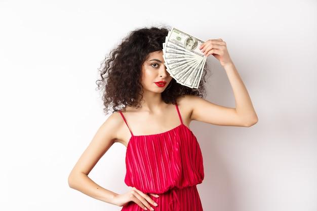Élégante femme aux cheveux bouclés en robe rouge, montrant un fan d'argent et l'air confiant. fille riche tenant des billets d'un dollar, fond blanc.