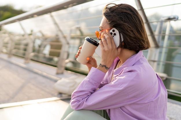 Élégante femme aux cheveux courts assis sur un pont moderne, profitant d'un café et utilisant un téléphone mobile