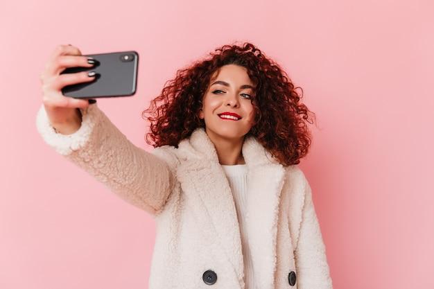 Élégante femme aux cheveux noirs bouclés portant un manteau de fourrure écologique se mord la lèvre et prend selfie sur l'espace rose.