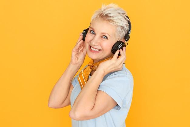 Élégante femme blonde à la retraite appréciant la musique, écoutant la radio dans des écouteurs sans fil posant contre jaune