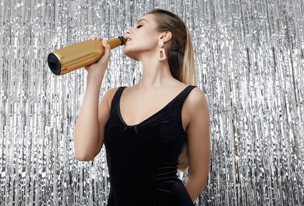 Élégante femme blonde sensuelle en robe noire avec une bouteille de champagne