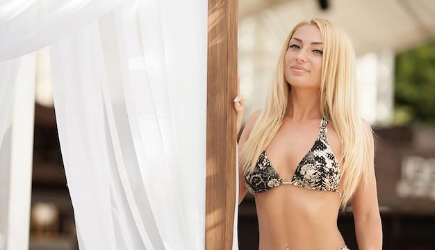 Élégante femme blonde sexy en bikini sur le corps mince et galbé bronzé pose près de la piscine.