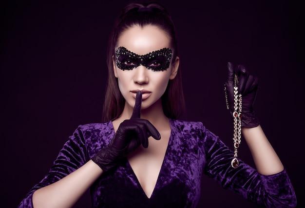Élégante femme brune en belle robe violette, masque de paillettes et gants noirs