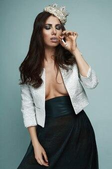 Élégante femme brune chaude en couronne d'or fumant une cigarette sur fond noir en studio